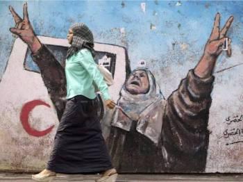 Seorang wanita Palestin berjalan di hadapan dinding dipenuhi lukisan mural di Gaza.