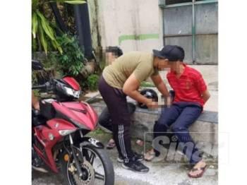 Kedua suspek ketika ditahan polis di belakang Maybank Pekan Kota Kemuning Seksyen 31 di sini.