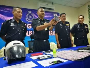 Razmi (tengah) menunjukkan gambar suspek pada sidang akhbar di Ibu Pejabat Polis Daerah Marang hari ini.