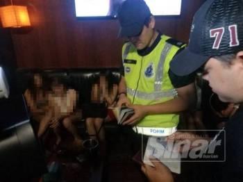 Polis menjalankan pemeriksaan dokumen wanita warga asing dalam serbuan di sebuah pusat hiburan di USJ21, Subang Jaya, malam tadi.
