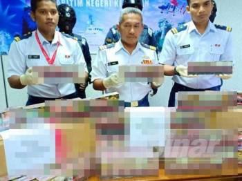 Ismail (tengah) menunjukkan rokok putih yang dirampas APMM semalam.