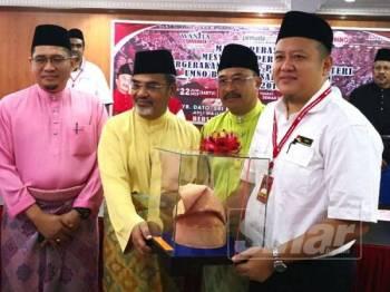 Rizam (kanan) menyampaikan cenderahati kepada Ahli Majlis Tertinggi UMNO, Datuk Seri Tajuddin Abdul Rahman pada Majlis Perasmian Mesyuarat Perwakilan Wanita, Pemuda dan Puteri UMNO Bahagian Sabak Bernam di Dewan UMNO Bahagian Sabak Bernam hari ini.