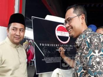 Mohd Asmirul (kanan) menandatangani plak perasmian Proriders Auto (M) Sdn Bhd. Turut sama Mohd Faiz (kiri).