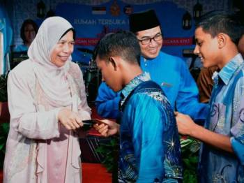 Zuraida Kamaruddin (kiri) menyampaikan sumbangan duit raya kepada golongan anak yatim pada Majlis Rumah Terbuka Perdana Aidilfitri Anjuran Gabungan NGO Penggerak Dasar Komuniti Negara KPKT di Balai Bomba dan Penyelamat Jasin Bestari, hari ini. - FOTO BERNAMA