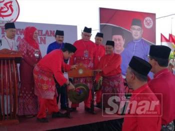 Noh (tengah) menyaksikan paluan gong sebagai simbolik perasmian Mesyuarat Perwakilan UMNO Bahagian Tanjong Karang yang disempurnakan Ahmad Maslan.