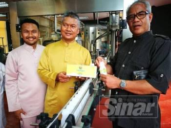 Muhammad Hariz (kiri) mengiringi Dr Mohd Termizi (kanan) melawat pusat pemprosesan susu berteknologi tinggi itu di Jenang.