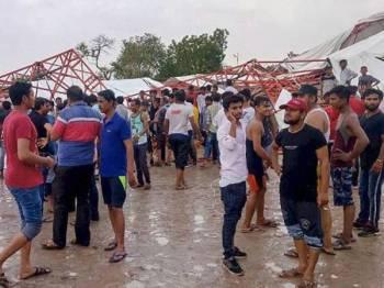 Orang ramai menanti pihak berkuasa melakukan operasi menyelamat di bawah runtuhan. Foto: The Indian Express