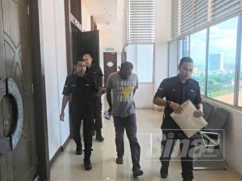 Tertuduh diiringi polis selepas prosiding selesai.