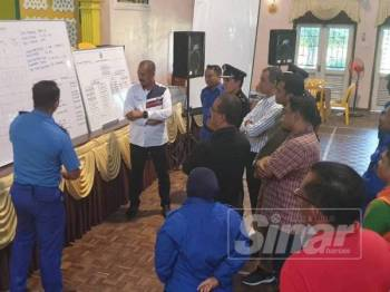 Abu Bakar meneliti taklimat kejadian banjir daripada seorang pegawai bomba di pusat pemindahan SMK Kedawang, Kuah, Langkawi, hari ini.