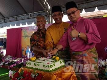 Wan Marzuki (kanan) memotong kek sebagai simbolik perasmian Majlis Hari Bersama Pelanggan dan Sambutan Hari Raya Aidilfitri PPD Kemaman.