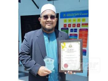 Mohammad Afdhaluddin menunjukkan anugerah Madrasah Tahfiz Cemerlang Peringkat Negeri Johor 2019 yang diberikan kepada MTAJ.