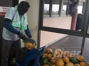 George membelah buah kelapa muda untuk diedarkan kepada petugas.