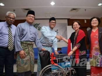 Ahmad Faizal menyempurnakan simbolik penyerahan kerusi roda kepada Pengarah HRPB, Dr Teo Gim Sian.