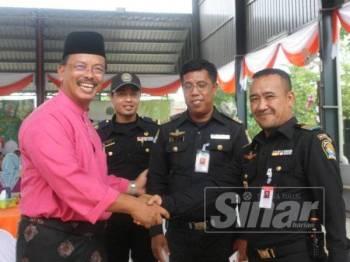 Mohd Azam (kiri) bersalaman dengan anggota penguatkuasaan dari Thailand yang hadir ke Majlis Sambutan Hari Raya Aidilfitri Maqis Wilayah Timur di Rantau Panjang.