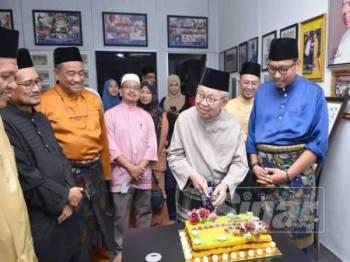 Tengku Razaleigh memotong pulut kuning simbolik perasmian Pertubuhan Kebajikan Asnaf Gua Musang (PEKA GM).