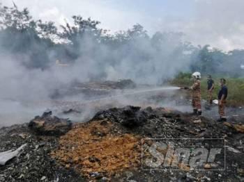 Anggota bomba sedang memadamkan kebakaran di atas tanah seluas suku ekar di Batu Lesung, Alor Gajah.