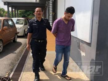 Tertuduh (kanan) dibawa keluar dari Mahkamah Sesyen selepas mengaku salah merompak kedai serbaneka di Pengkalan Chepa.