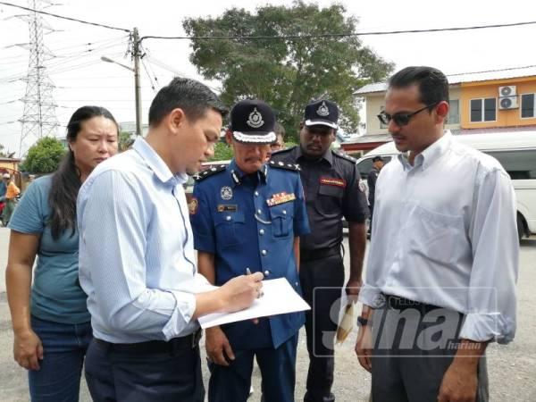 Zulkurnain (kiri) menyemak jumlah premis yang diarah tutup dalam operasi bersepadu di Serdang Jaya 5 dan 6 hari ini.