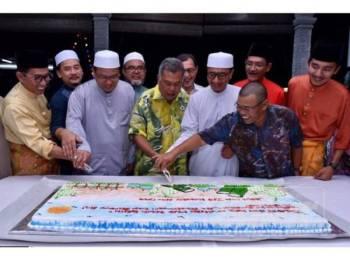 Muhammad Khalil (empat, kanan) bersama barisan kepimpinan kedua-dua parti memotong kek sempena sambutan Hari Raya Aidilfitri UMNO Bahagian Kuala Terengganu.