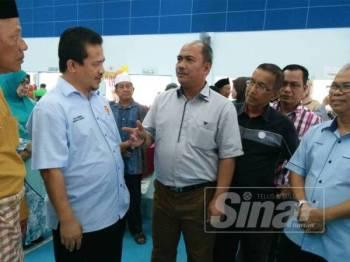 Azman (dua kiri) sempat bertanyakan sesuatu kepada Ketua Pengarah Lembaga Kemajuan Ikan Malaysia (LKIM, Jamaluddin Othman (tiga kiri) yang turut hadir ke Jamuan Aidilfitri LKIM di Kuala Kedah, semalam.