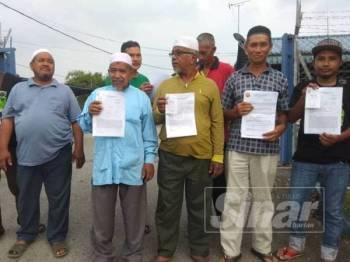 Mohd Sabri dua kanan bersama penduduk menunjukkan laporan polis dibuat