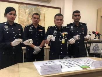 Abdul Rahim (dua, kanan) bersama barisan pegawai menunjukkan dadah yang berjaya dirampas daripada empat suspek dalam dua serbuan berasingan Isnin lalu dan semalam.