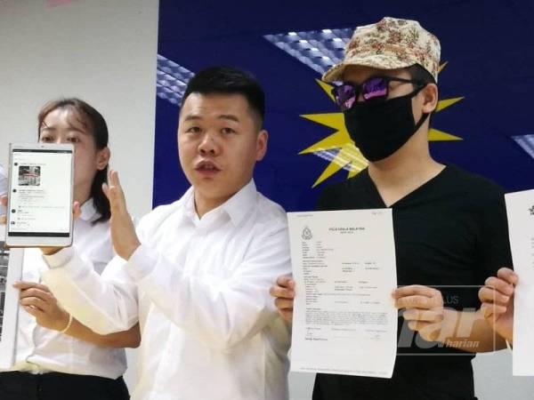 Leong (bertopeng) dan Guo Nan bersama laporan polis pada sidang media berkenaan.