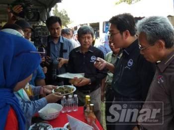 Tze Tzin (dua dari kanan) mencuba produk dihasilkan Jabatan Perikanan ketika melawat ruang pameran agensi di bawah Kementerian Pertanian dan Industri Asas Tani.