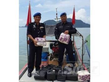 Rohizan (kiri) dan anggota polis Marin menunjukkan sebahagian beras pulut yang dirampas dari sebuah bot.
