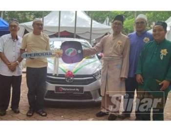 Nek Fauji (dua dari kiri) menerima replika kunci hadiah kereta Perodua Axia yang dimenangi dalam cabutan bertuah My Hartanah.