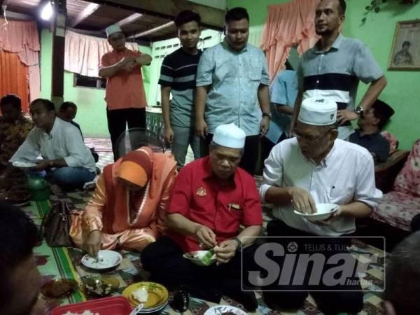 Mohamad Sabu (duduk, tengah) menikmati pulut nyior sambil diperhatikan Mohd Hanif berdiri (tengah).