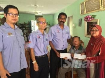 Anthony (tengah) menyampaikan cek kepada Abdul Rahman dan Zainab di kediaman mereka di Kampung Tanjung Tualang semalam.