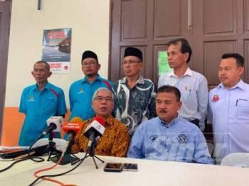 Hassan (duduk,kiri) ketika berucap pada sidang media, di sini hari ini.