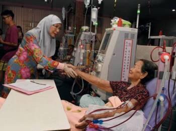 Dr Wan Azizah bersalaman dengan warga emas, Tan An Nya,81, yang melakukan hemodialisis pada lawatan di Pertubuhan Hemodialisis Seberang Perai Selatan hari ini. -Foto Bernama