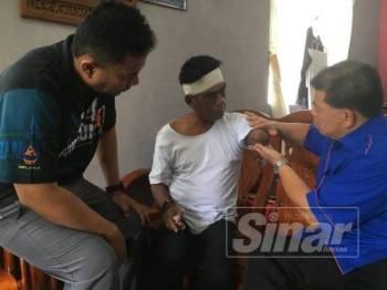 Roslan (kanan) bersama Effendy menziarahi Ishak, anggota APM yang kehilangan tangan kiri selepas terpaksa di potong akibat kemalangan jalan raya lebih sebulan lalu.