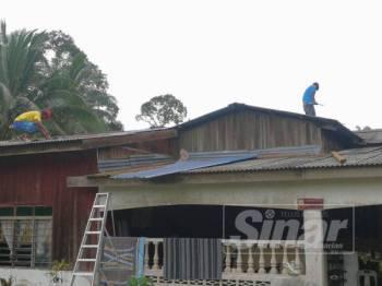 Penduduk dengan bantuan saudara-mara membaiki kerosakan bumbung akibat ribut Jumaat lalu.
