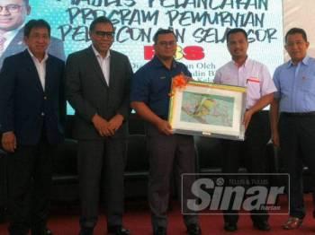 Amirudin (tengah) menerima cenderahati disampaikan Yang Dipertua Majlis Daerah Hulu Selangor (MDHS), Shukri Mohamad Hamin selepas merasmikan majlis pelancaran progran P3S, hari ini.