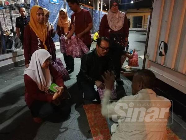 Zamrud ( tengah) bertanyakan sesuatu kepada gelandangan ketika program menyantuni mereka diadakan di CIQ Johor Bahru.
