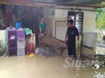 Zuraidi melihat motosikal miliknya yang tidak sempat dialihkan dan mengalami kerosakan teruk akibat banjir.