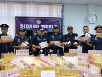 Mohd Rakbi (tiga, kiri) bersama pegawai dan anggota JKDM menunjukkan rokok seludup yang dirampas.