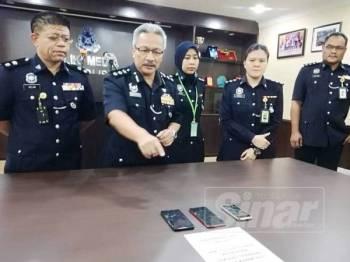 Wan Rukman (dua dari kiri) menunjukkan tiga telefon bimbit, dua daripada milik suspek dan sebuah lagi mangsa dirampas untuk tujuan siasatan.