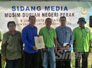 Nor Sam (kiri) melihat Exco Kemudahan Awam, Infrastruktur, Pertanian dan Perladangan Negeri, Abdul Yunus Jamhari (dua dari kiri) menyampaikan sijil kepada pemilik durian pada majlis berkenaan.