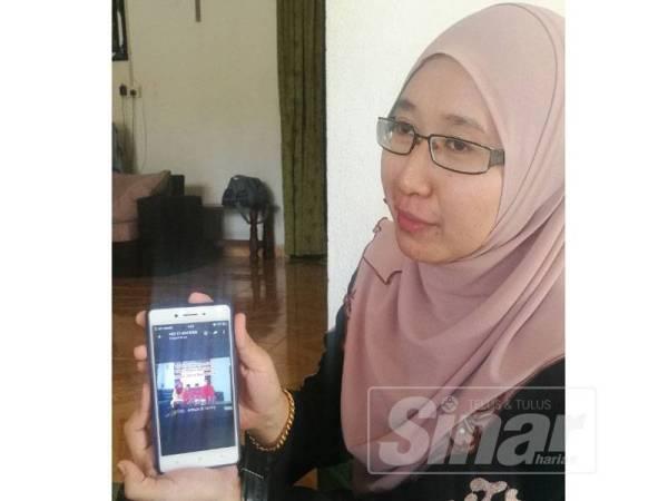 Siti Nurhayati menunjukkan gambar keluarga yang dirakam ketika Aidilfitri lalu bersama arwah suaminya dan anak-anak.