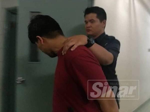 Tertuduh mengelak daripada wajahnya dirakamkan petugas media di Mahkamah Majistret Shah Alam, hari ini.