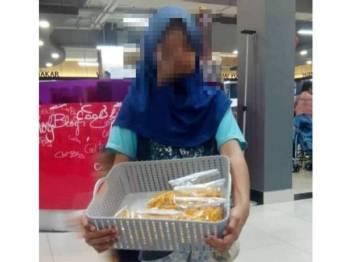 Kanak-kanak berusia 12 tahun ini menjaja makanan ringan di sekitar pasar raya di Bandar Rawang. - Foto: LZS