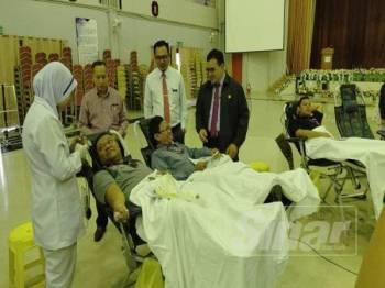 Mohd Fikri (kanan) bersama pelajar yang sedang menderma darah pada Program Derma Darah Perdana PSMZA.