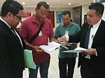 Mohd Hazwan (kanan) bersama Nuzul Fitri (kiri) menjelaskan sesuatu kepada dua wakil plaintif, Abu Bakar Mat Ali, 50, (dua dari kanan) dan Wan Mohd Ruslan Wan Abdullah, 38, selepas selesai memfailkan writ saman di Mahkamah Tinggi Kuala Terengganu hari ini.