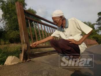 Md Isa menunjukkan bahagian jambatan yang dipateri bagi membolehkan penduduk terus menggunakan jambatan berkenaan.