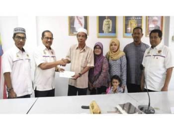 Ab Aziz (dua kiri) menyampaikan sumbangan cek bernilai RM1,000 kepada Ab Rahim (tiga kiri).