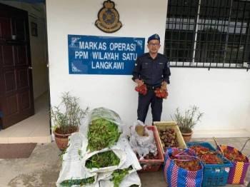Anggota polis marin menunjukkan barangan yang dirampas dari sebuah bot dalam cubaan menyeludup masuk ke negara ini.
